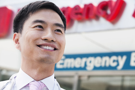 above 30: Portrait of smiling doctor outside of the hospital, emergency room sign in the background, Close-Up