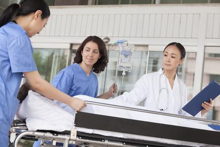 paciente en camilla: Param�dicos m�dico femenino y que giraban en un paciente en una camilla en la puerta del hospital