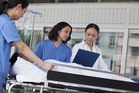 Paramedics and doctor looking down at the medical record of patient on a stretcher in front of the hospital Banco de Imagens