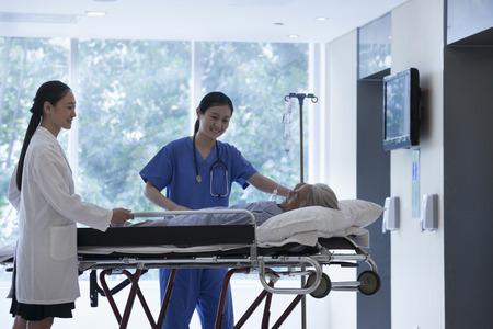 Female doctor and nurse wheeling a stretcher with a patient in the halls of the hospital