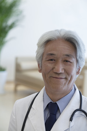above 30: Portrait of mature doctor looking at camera and smiling