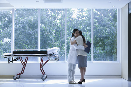 doctoras: Doctor y abrazos paciente en un hospital junto a una camilla, de cuerpo entero