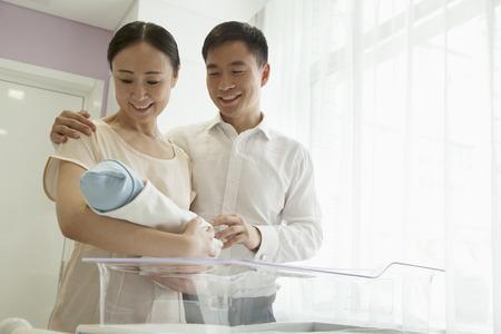 sala parto: Giovane azienda il loro neonato nella nursery dell'ospedale famiglia felice