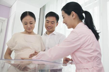 sala parto: Nurse toccando pancia della donna incinta in ospedale con il marito accanto a lei