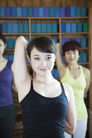 Three young women stretching and doing yoga, looking at camera,