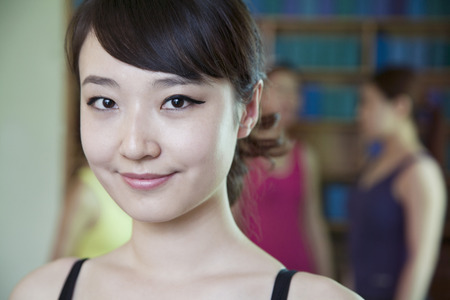 above 25: Portrait of smiling young woman in a yoga studio