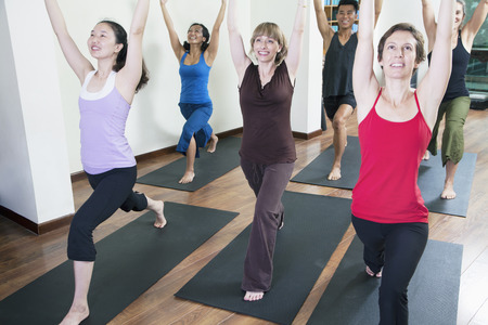 class a: Group of people with hands raised doing yoga during a yoga class