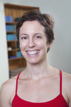 Portrait of smiling woman in a yoga studio, head and shoulders Stock Photo