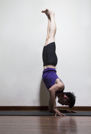 above 25: Upside down man doing yoga in a yoga studio, side view Stock Photo