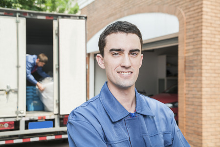 above 25: Portrait of smiling mover with moving truck in the background Stock Photo