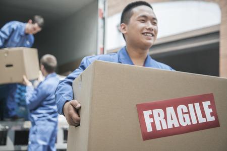 Movers Entladen eines Möbelwagen und mit einem fragile box