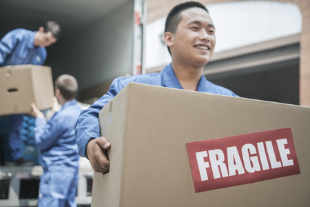 Movers unloading a moving van and carrying a fragile box