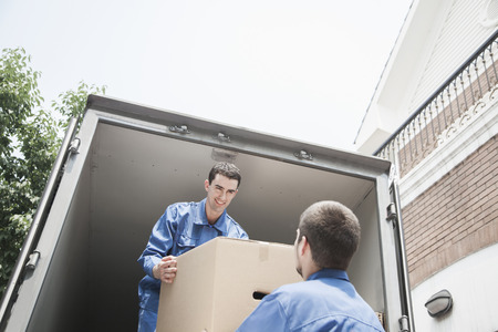 people moving: Movers unloading a moving van, passing a cardboard box