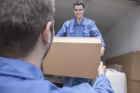 pappkarton: Movers Entladen eines M�belwagen, vorbei an einem Karton Lizenzfreie Bilder