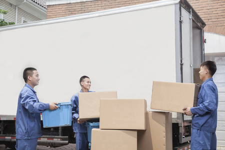 unloading: Movers unloading a moving van, many stacked cardboard boxes Stock Photo
