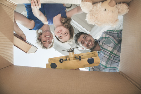 three day beard: Smiling family looking into a cardboard box, view from directly under Stock Photo