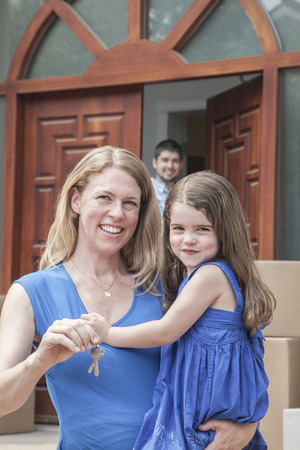 some under 18: Mother and daughter smiling and holding the keys to their new house