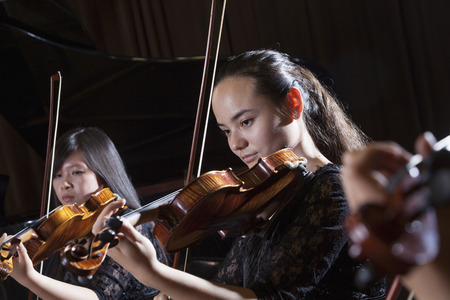 above 18: Violinists playing during a performance, head and shoulders Stock Photo