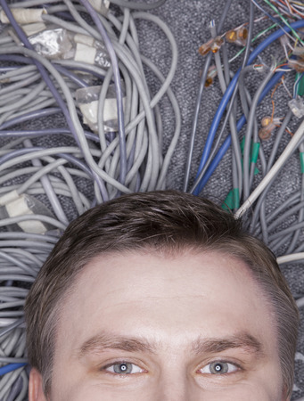 plugging: Businessmans face lying down on computer cables looking up, half