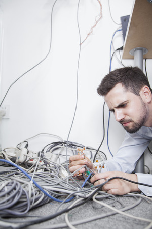 man lying down: Frustrated man lying down trying to figure out and sort  computer cables Stock Photo
