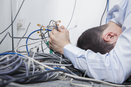 Frustrated man lying down trying to figure out and sort  computer cables Stock Photo