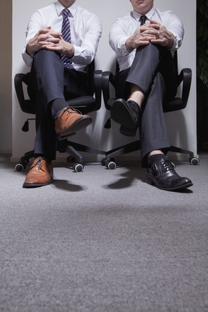 legs crossed: Two businessmen sitting down with legs crossed, low section