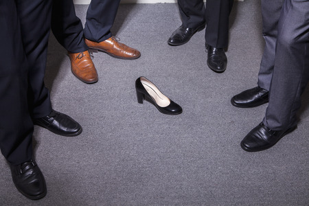 battle of the sexes: Businessmen standing in a circle around a womans high heel, feet and legs only Stock Photo