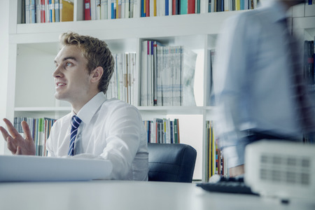 above 21: Young businessman discussing at a business meeting with colleague behind him Stock Photo