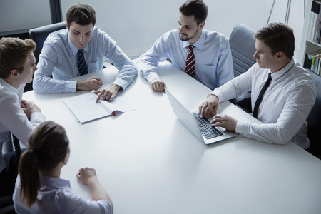 above 21: Five business people having a business meeting at the table in the office