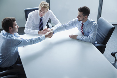 corporate business: Businessmen shaking hands over the table in the office Stock Photo