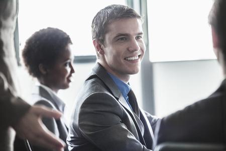 hombres jovenes: Grupo de empresarios sentado y sonriente en una reuni�n de negocios