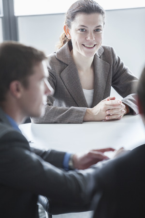 Three smiling business people sitting at a table and having a business meeting in the office photo