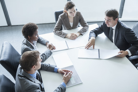 above 18: Four business people sitting around a table and having a business meeting, high angle view