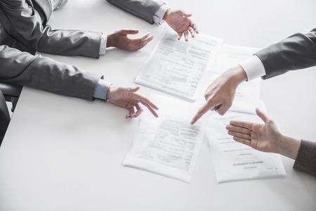 personas discutiendo: Cuatro hombres de negocios y argumentando insinuar alrededor de una mesa durante una reuni�n de negocios, las manos s�lo