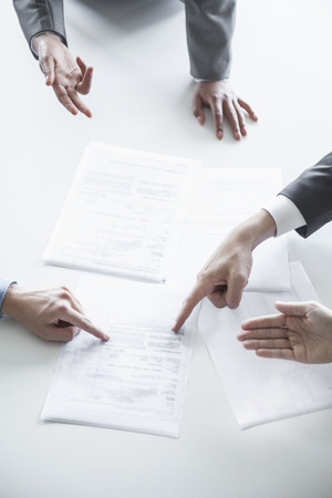 business meeting: Four business people arguing and gesturing around a table during a business meeting, hands only  Stock Photo