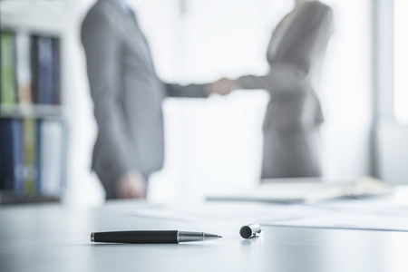 young business: Two business people shaking hands in the background, pen lying on the table in the foreground