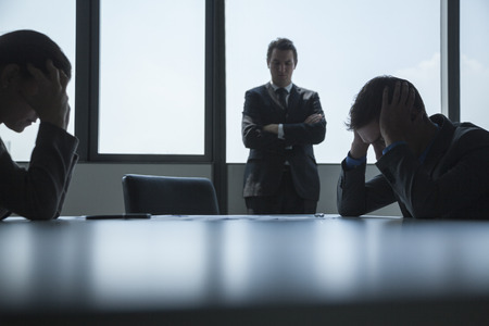 Three frustrated and overworked business people in the board room with arms crossed and head in hands.  photo