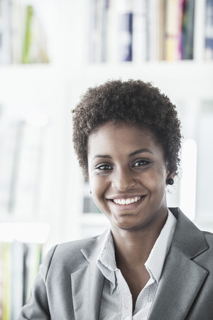 Portrait of smiling young businesswoman with short hair looking at the camera, head and shoulders photo