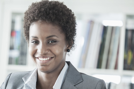 african business: Portrait of smiling young businesswoman with short hair looking at the camera, head and shoulders