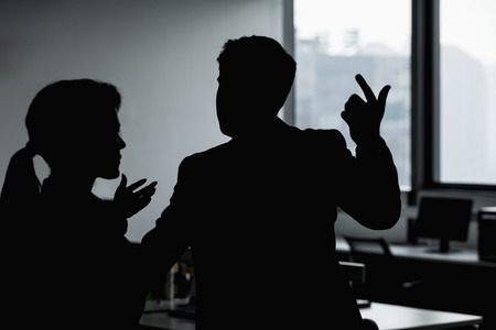 above 18: Silhouette of two business people gesturing and arguing in the office