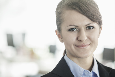 bangs: Portrait of smiling young businesswoman with bangs looking at the camera, head and shoulders