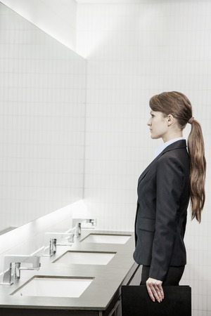mirror image: Young businesswoman with long hair looking into the mirror and preparing herself in the bathroom