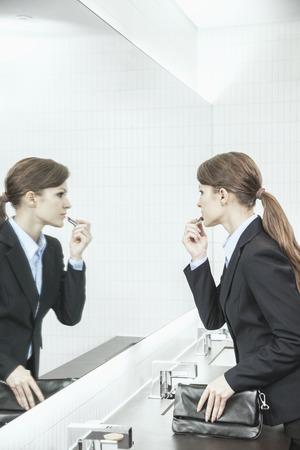 espejo: Empresaria joven con el pelo largo que mira en el espejo y pintarse los labios en el ba�o Foto de archivo
