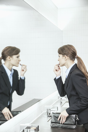 mirror: Young businesswoman with long hair looking into the mirror and putting on lipstick in the bathroom