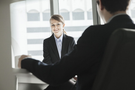above 18: Two business people sitting, smiling and looking at each other during a business meeting
