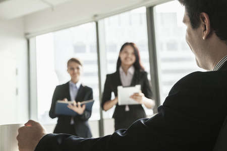 above 18: Two businesswomen standing up and presenting during a business meeting as a businessman watches