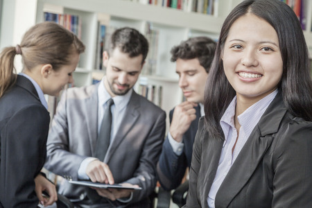 above 18: Business woman smiling and looking at the camera with her colleagues talking and looking down at a digital tablet in the background