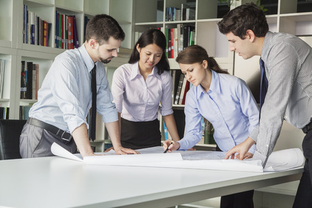 Four architects standing and planning around a table while looking down at blueprint photo