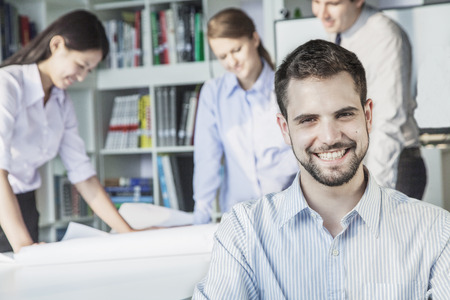 Smiling architect looking at camera while colleagues are planning around a table and looking at a blueprint photo