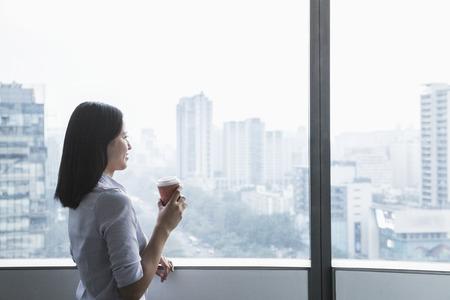 adentro y afuera: Empresaria joven sonriente que sostiene una taza de caf� y mirando por la ventana de un paisaje urbano en Beijing, China Foto de archivo
